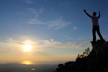 man standing on a mountain top with raised hands  to God  with rising / setting sun in the background