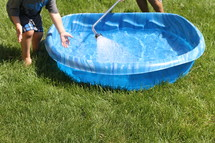 children filling a plastic swimming pool with water