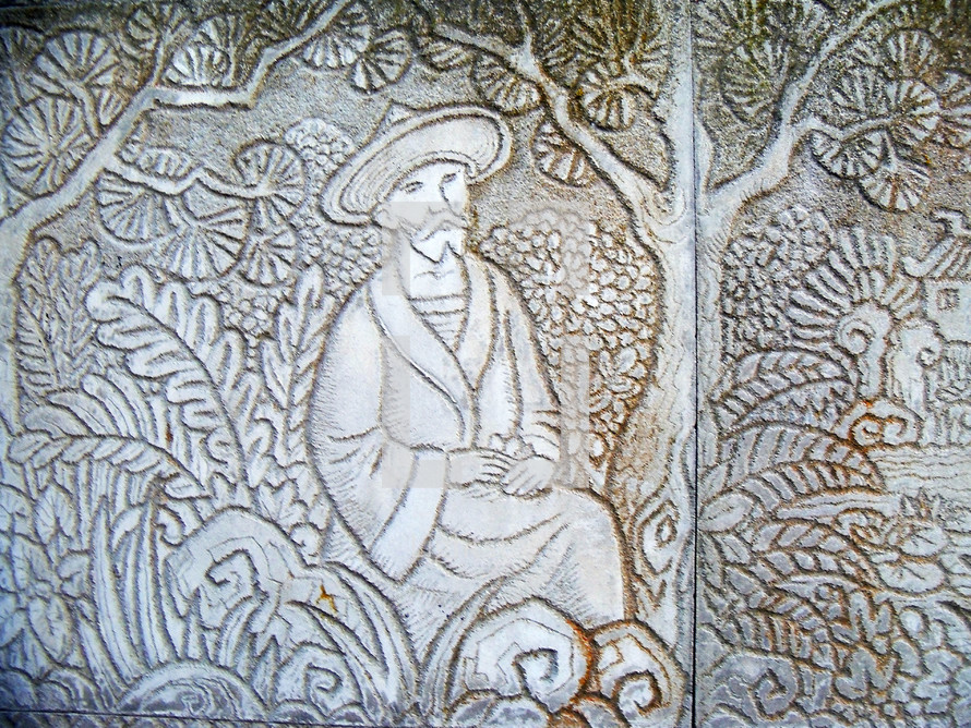 A carved relief of a peasant man sitting in a field with ferns, trees and vegetation. The peasant represents the world and the field represents the world where we are to go out and spread the gospel to all men.