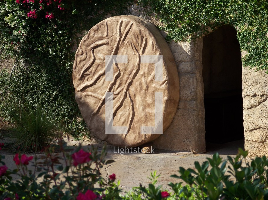 Roll away the stone! The stone that sealed Jesus tomb was rolled away and Jesus arose from the grave after three days, just as He said He would. Beautiful image of Jesus tomb covered in vines, flowering plants and sun and shade.