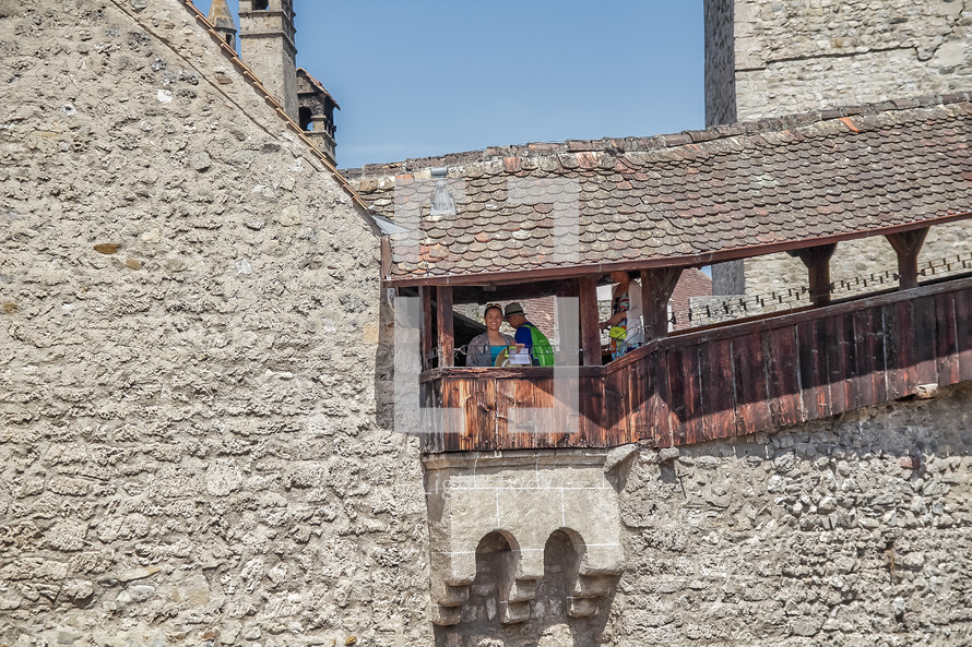 people overlooking a railing on a castles fortress walls