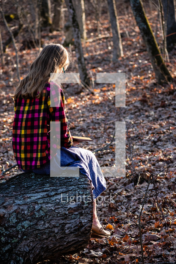 girl reading a Bible outdoors
