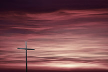 cross against a purple sky at sunset