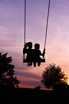 silhouettes of children on a swing