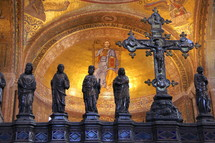 Decorative cross with statures of disciples and saints in a cathedral dome.