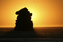 sun glowing behind  a rock