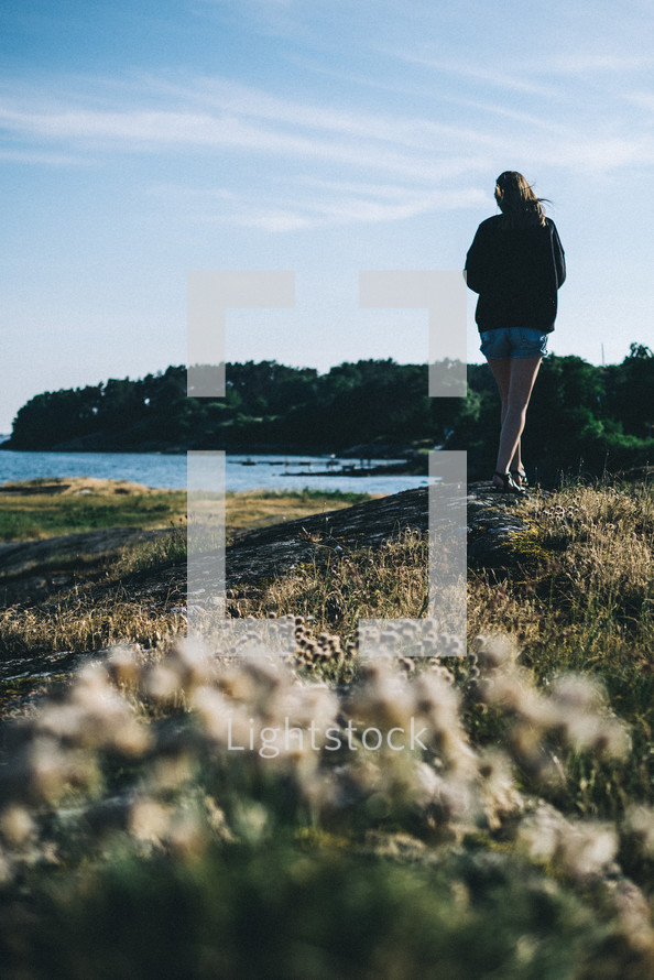 a woman standing on a shore looking out at the water in Lysekil, Sweden