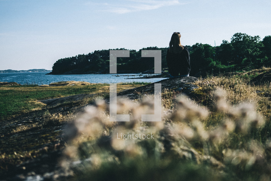 a woman sitting on a shore looking out at the water in Lysekil, Sweden