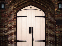 Large white wooden doors in an arched brick entryway.