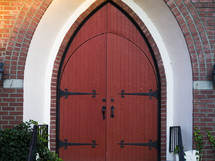 Large red doors in an arched brick entryway.