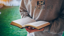 teen boy in a sweatshirt reading a Bible