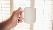 a man holding a coffee mug