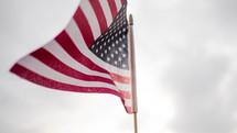 American flag against an overcast sky