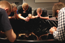 Young men sitting and praying together.