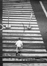 An elderly man crossing the street alone at a crosswalk