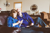 Couple sitting on a sofa looking at a cell phone.