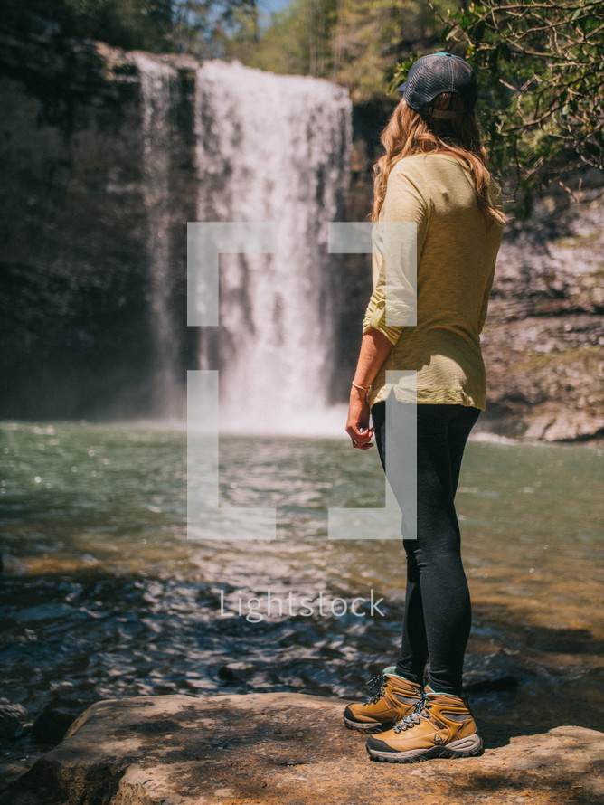a woman standing in front of a waterfall