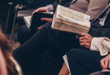 elderly couple with Bibles in their laps at church