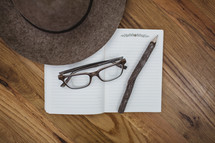 reading glasses, hat, pencil, and notebook on a wood floor