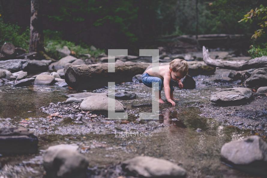 toddler boy exploring a stream