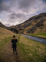 a woman walking on a path beside a mountain stream