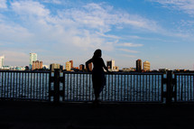 silhouette of a woman looking out at water
