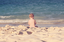 naked toddler sitting on a beach