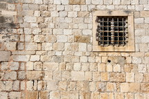 Barred window in ancient stone wall