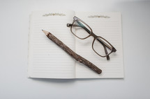 reading glasses and carved pencil on a notebook