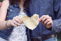 a couple holding a heart shape fall leaf