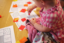 child playing with cut paper and a glue stick
