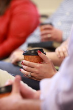 Female hands holding coffee cup and Bible during Bible study.