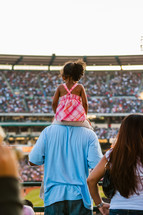 Young girl sitting on father shoulders at crusade dad
