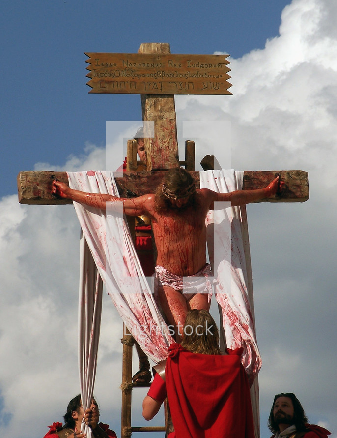 Roman soldiers take down the body of Jesus Christ after being crucified on the cross