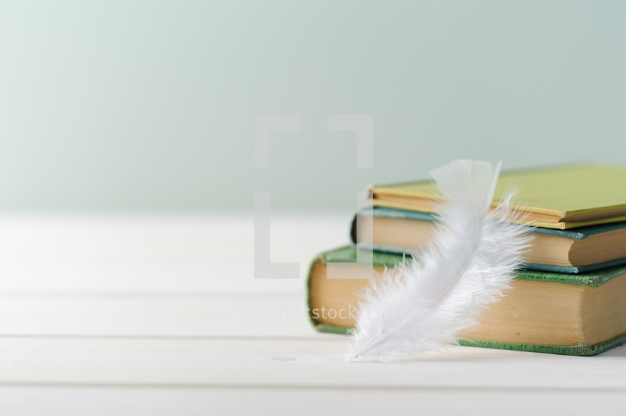 feather and a stack of books