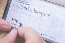 man writing a check to a church
