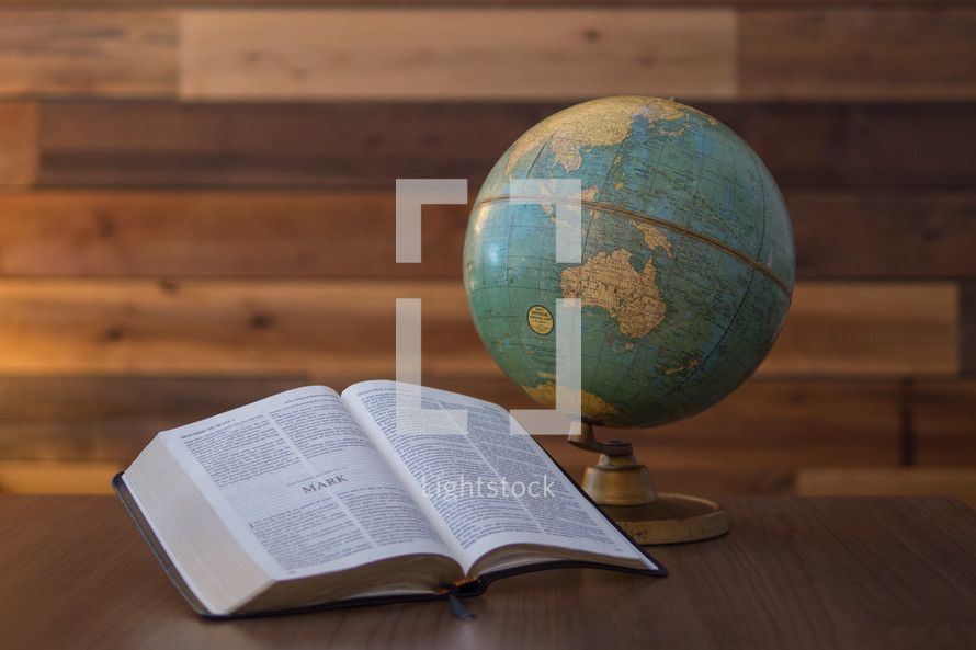 A Bible opened up to the great commission in front of a vintage globe.