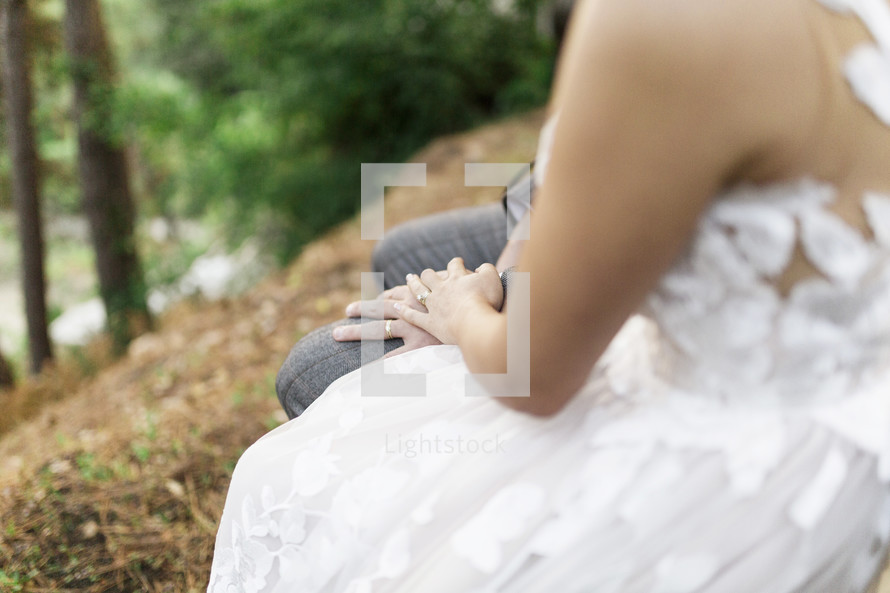bride and groom sitting on a bench outdoors
