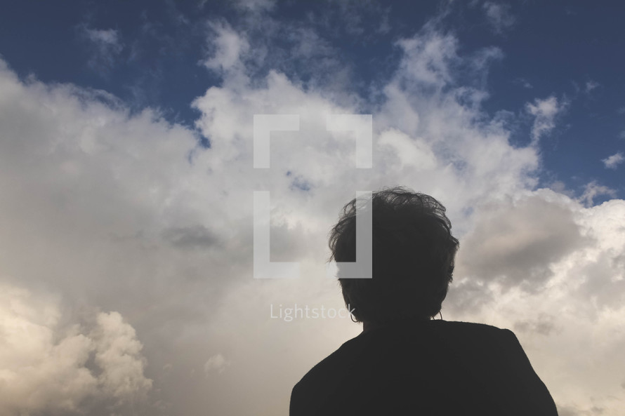 silhouette of a woman looking up at the sky