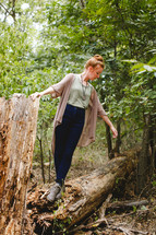 woman standing on a fallen tree in a forest alone