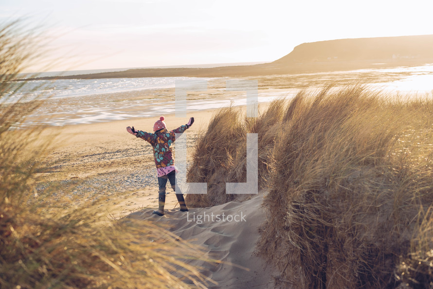 a girl child standing on a beach in a winter coat
