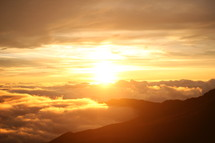 sun setting above the clouds