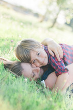 a mother and son hugging lying in the grass