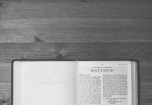 Bible open to Matthew on a wooden table.