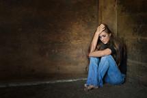 scared woman hiding in a corner