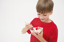 boy child eating a bowl of ice cream