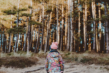 a girl in a coat walking into a forest
