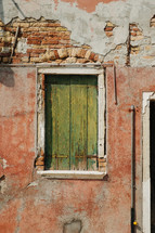 green shutters on an ancient building