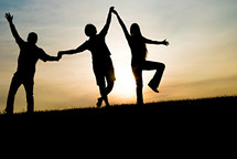 silhouettes of a father and his teenage children holding hands