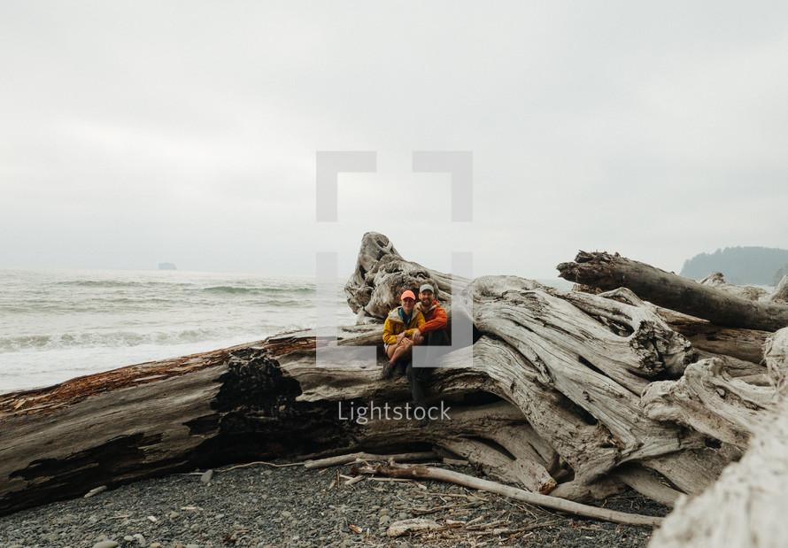 a couple on driftwood on a beach